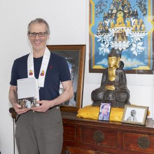 Dharmapriya with Volume 22 of The Complete Works of Sangharakshita, In the Sign of the Golden Wheel. Photo credit: Carolin Ubl