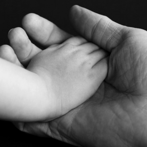 Child's hand in adult hand