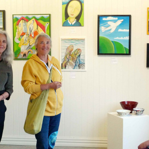 Kathleen (left) and Taralila (middle) with Suzie (sitting) at the opening - with David's paintings